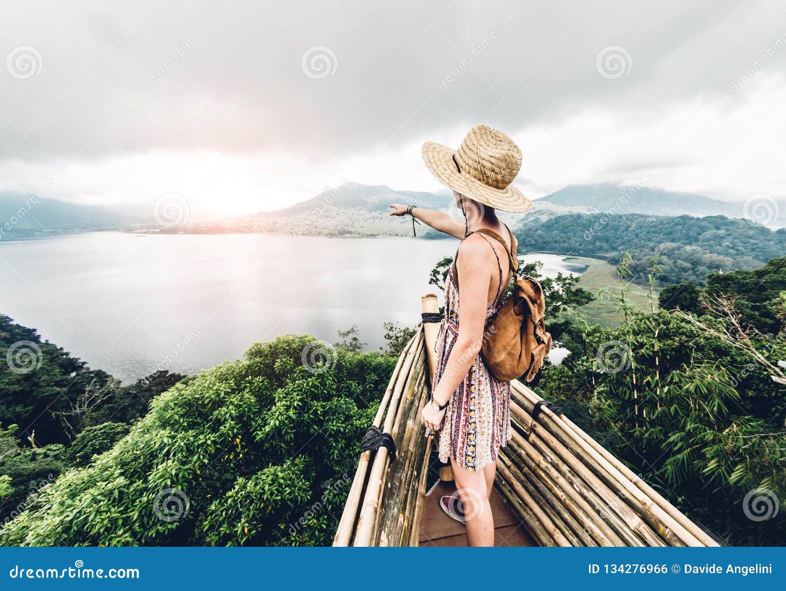 Mujer feliz que señala el horizonte que siente libremente que viaja el mundo en un fondo inspirado