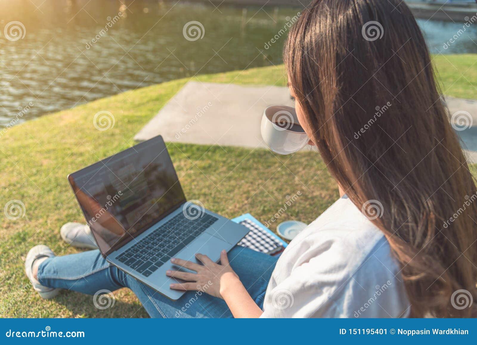 Mujer feliz que usa el ordenador portátil en el parque, entonado intencionalmente