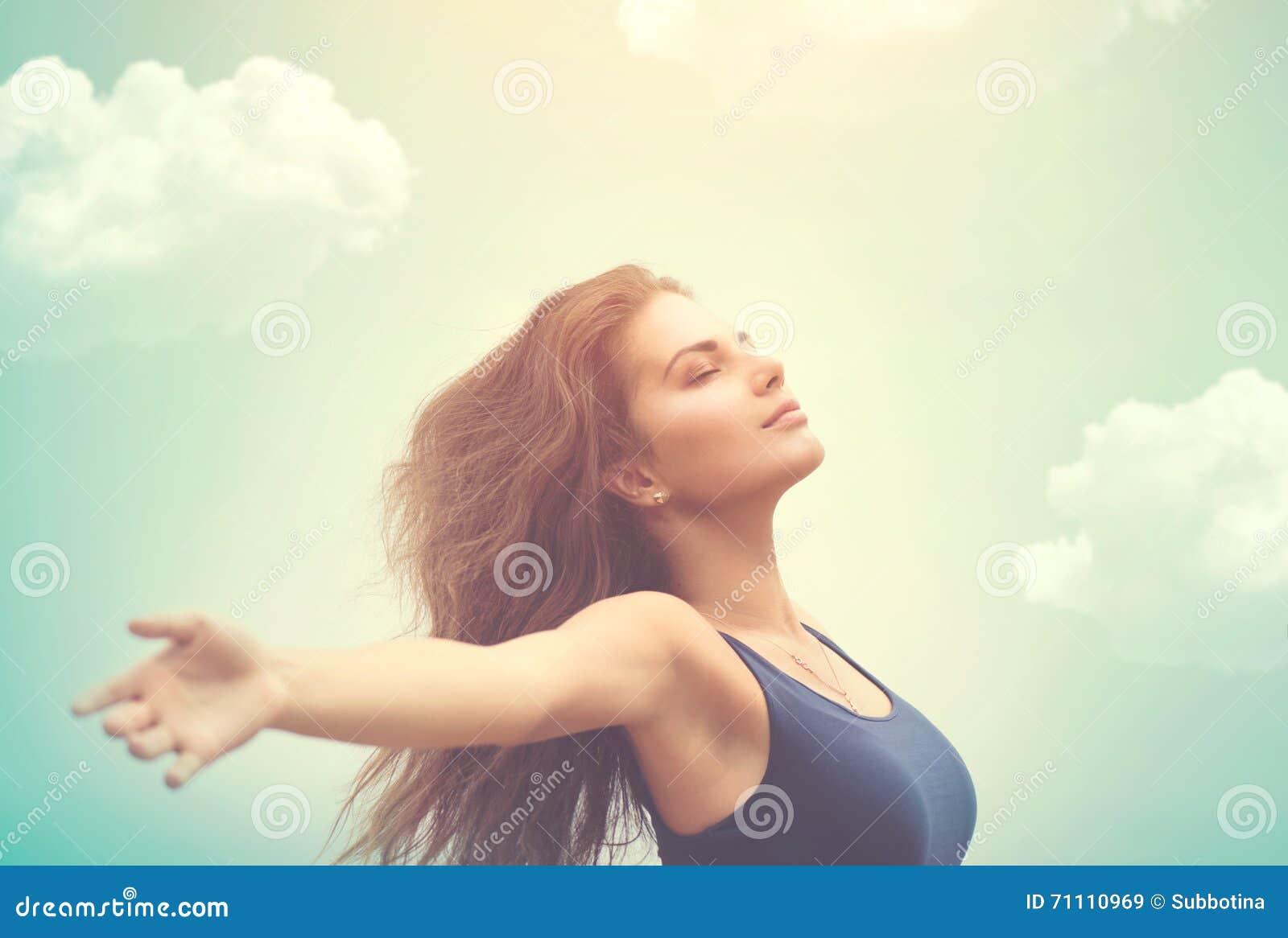 Mujer feliz sobre el cielo y el sol