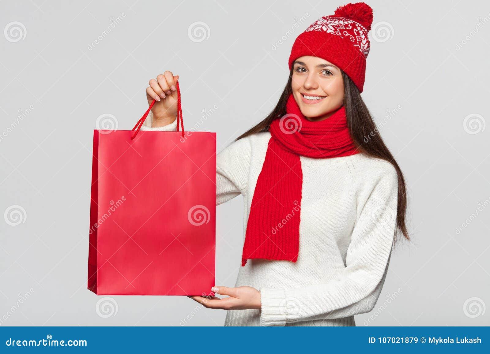 Mujer feliz sorprendida que sostiene el bolso rojo en el entusiasmo, haciendo compras Muchacha de la Navidad en venta del inviern