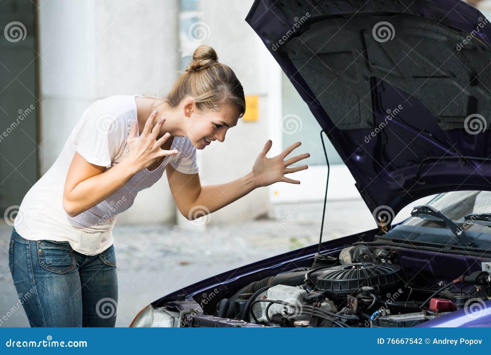 Mujer frustrada que mira el motor de coche analizado