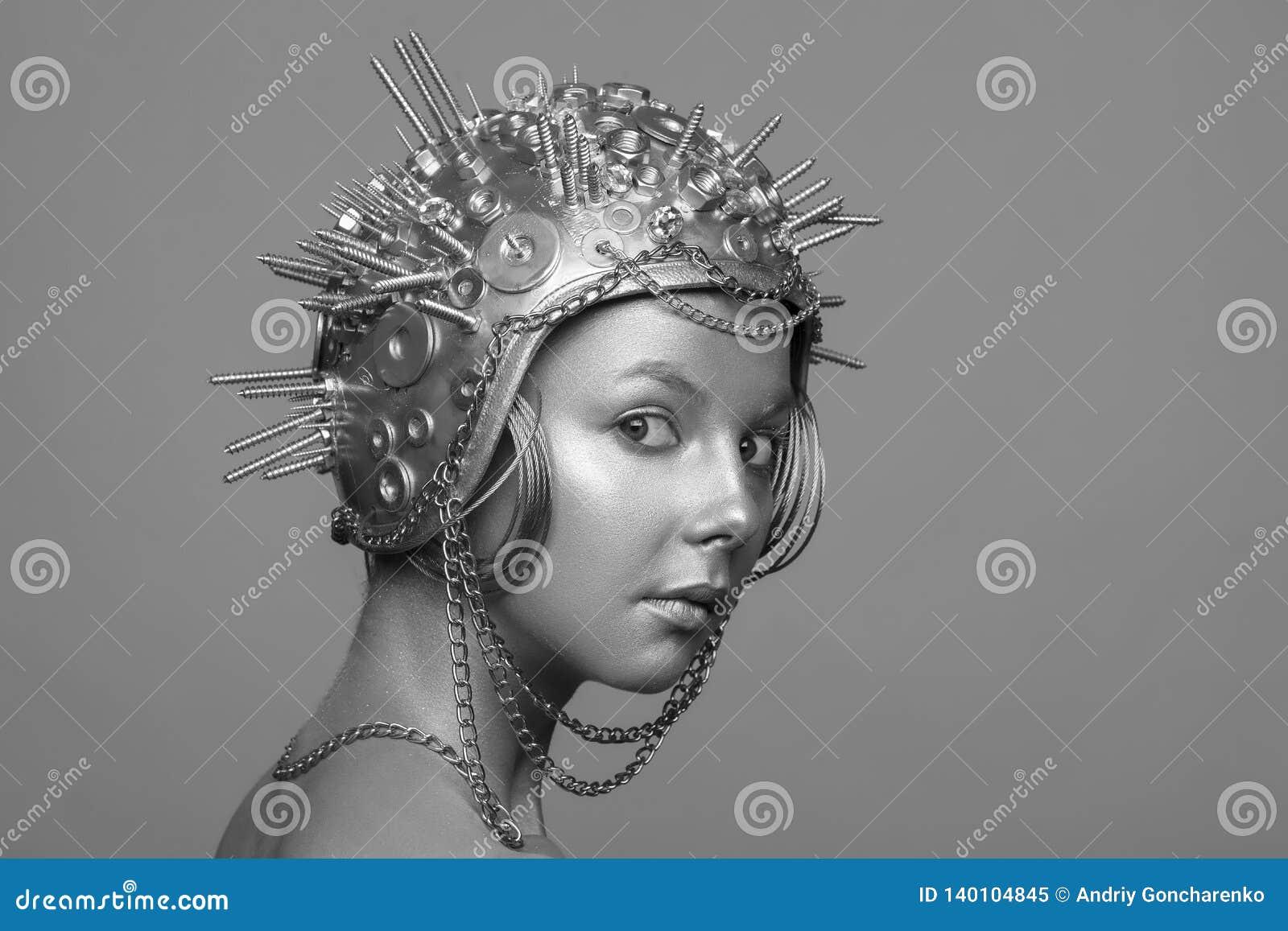 Mujer futurista en casco del metal con los tornillos, las nueces y las cadenas
