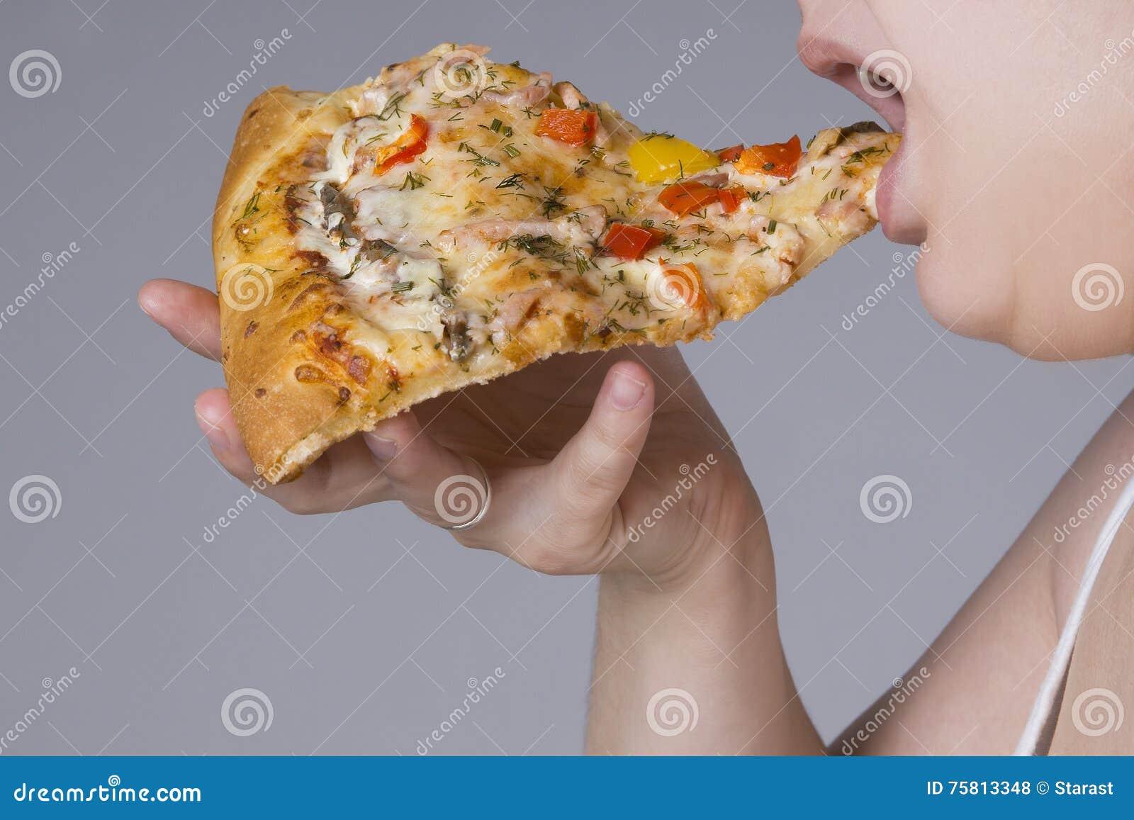 Mujer gorda con un pedazo de pizza a disposición, concepto de la obesidad