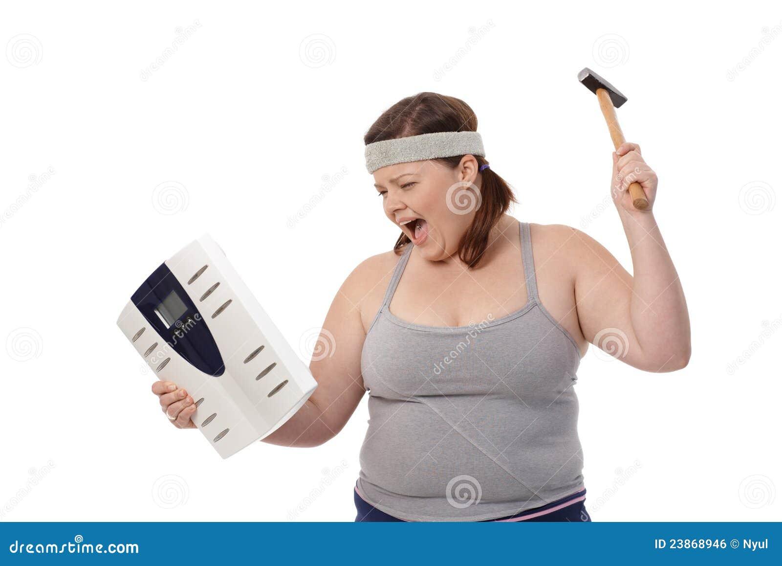 Mujer gorda enojada con el martillo y la escala