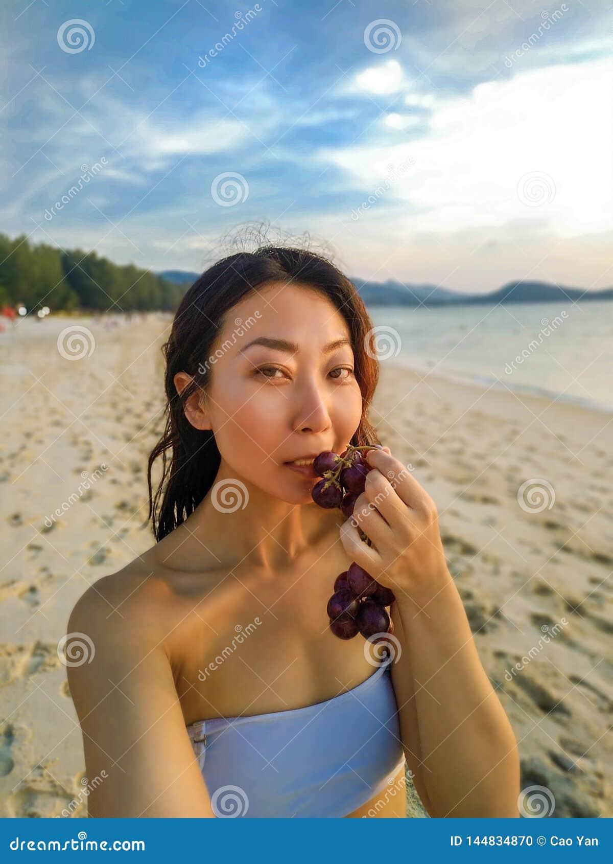 Mujer hermosa asiática en la playa que toma un selfie en día de fiesta