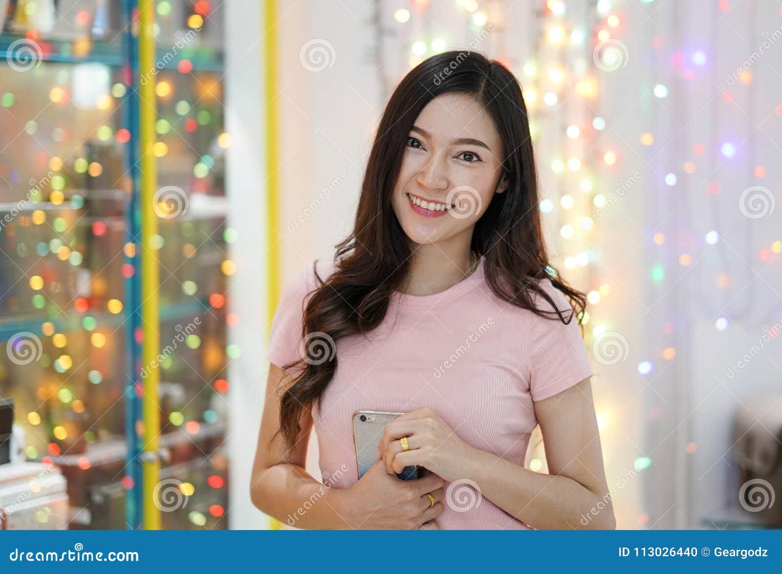 Mujer hermosa con el fondo del bokeh de la sonrisa y de la luz