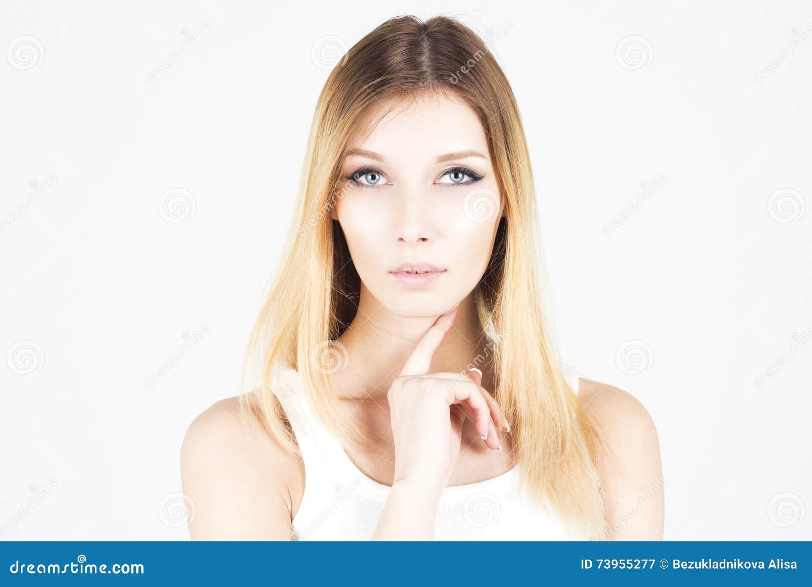 Mujer hermosa con el maquillaje permanente que sostiene el finger debajo de su barbilla