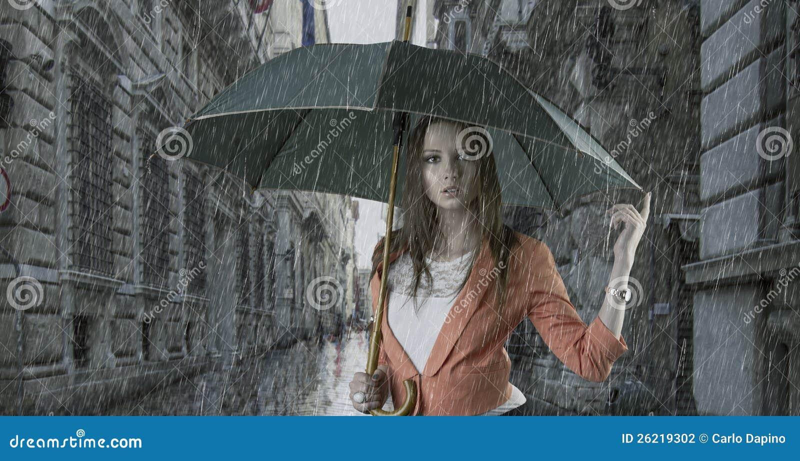 Mujer hermosa con el paraguas en ciudad bajo la lluvia