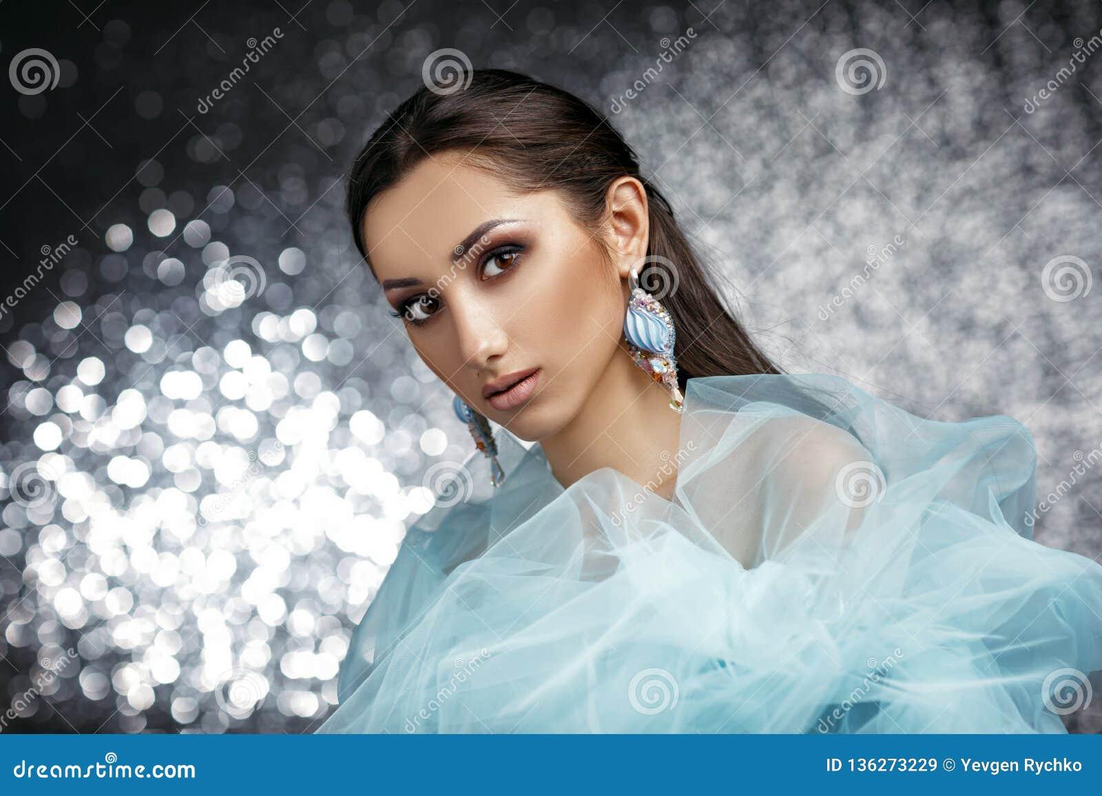 Mujer hermosa con el pelo hermoso, maquillaje y con los pendientes de lujo