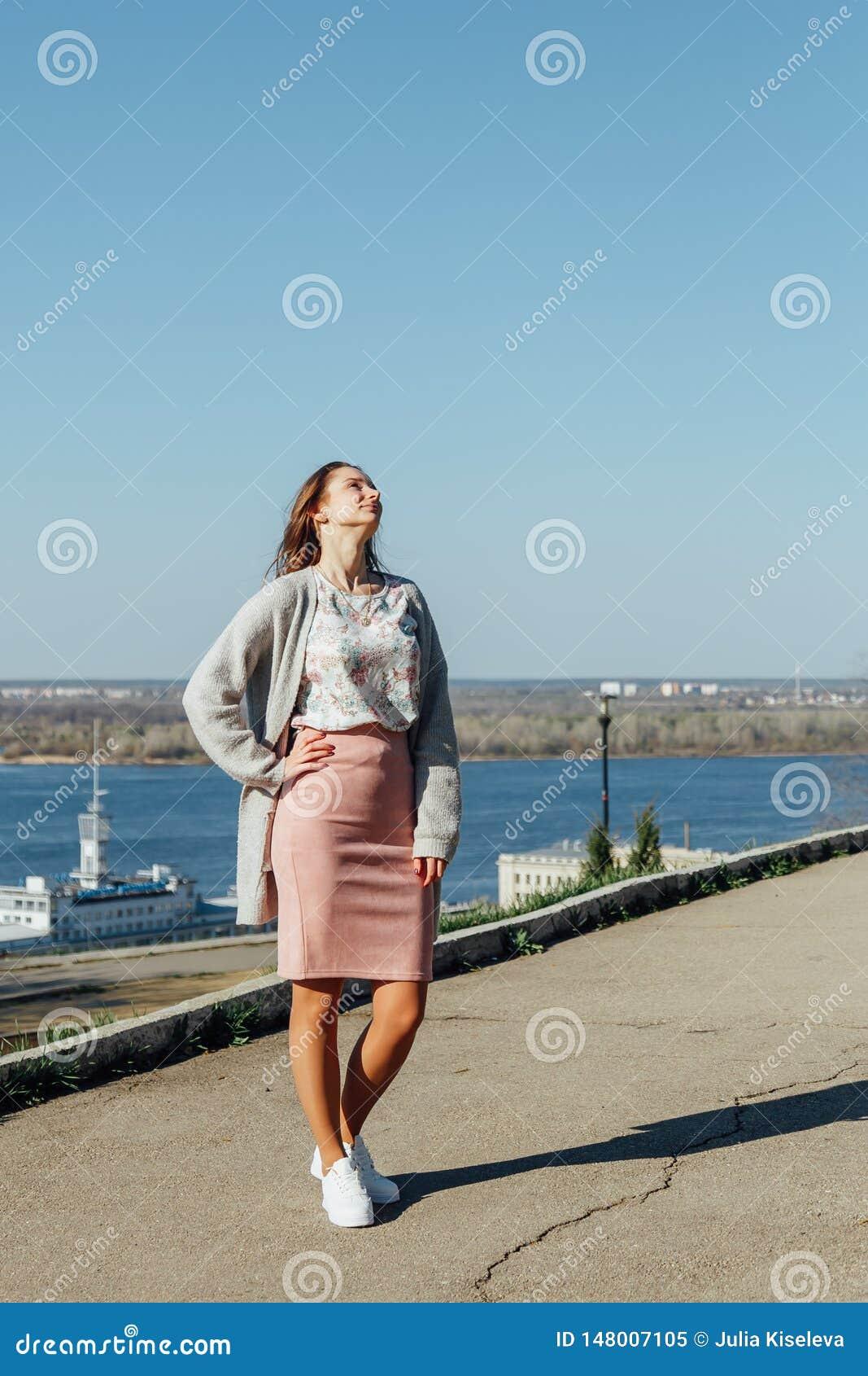 Mujer hermosa con el pelo largo que disfruta de la opini?n de la ciudad del puente en un d?a soleado