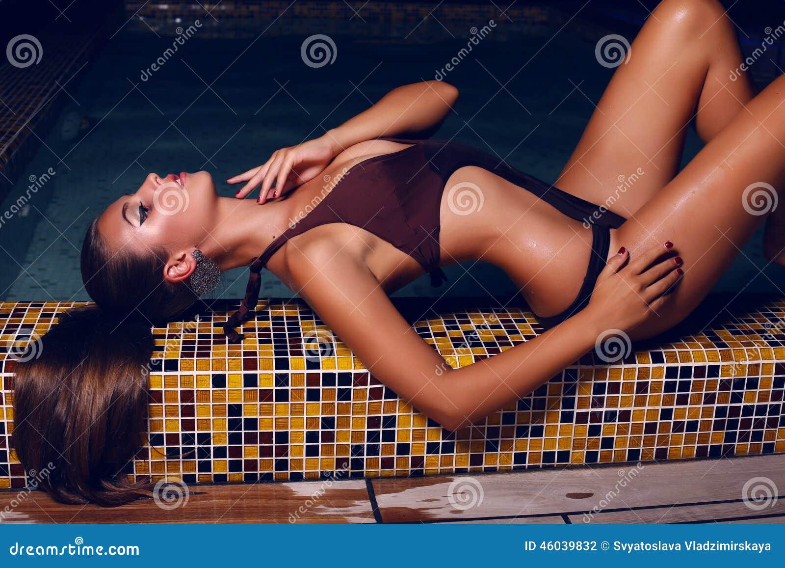 b71851de116f Mujer hermosa con el pelo oscuro en el bikini que presenta en piscina de la  noche