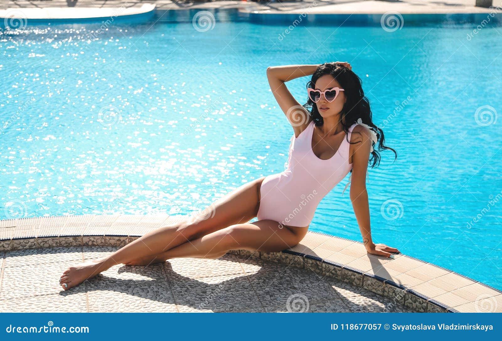 Mujer hermosa con el pelo oscuro en el traje de natación elegante que se relaja