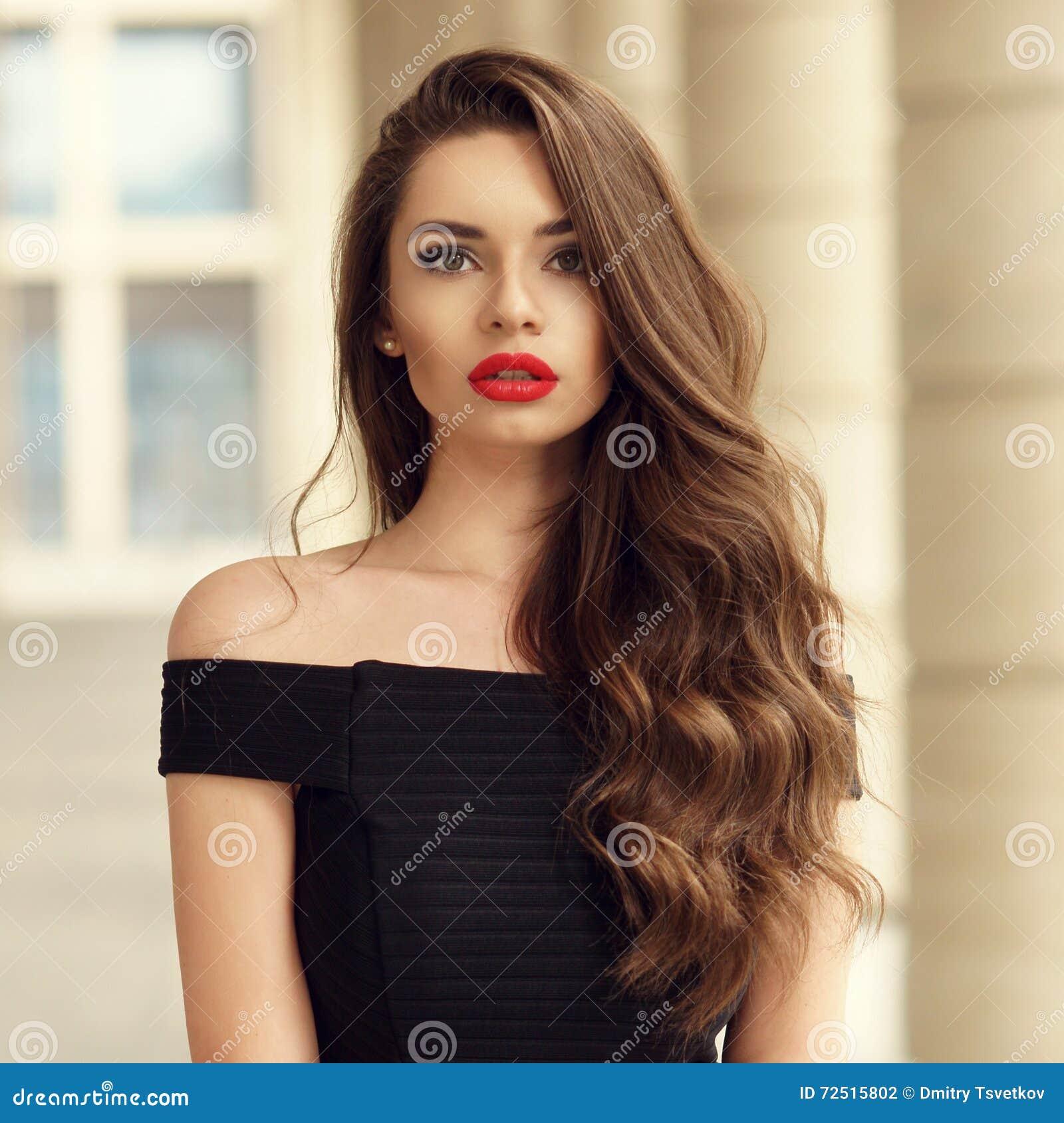 Mujer hermosa con el pelo rizado moreno largo