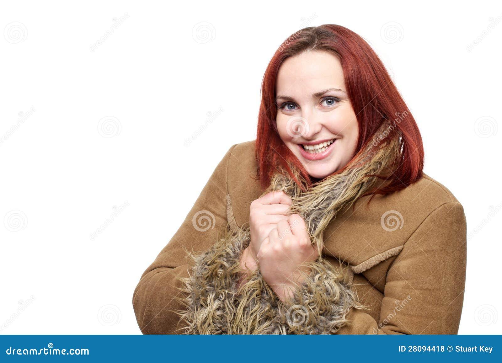Mujer hermosa con el pelo rojo en abrigo de invierno