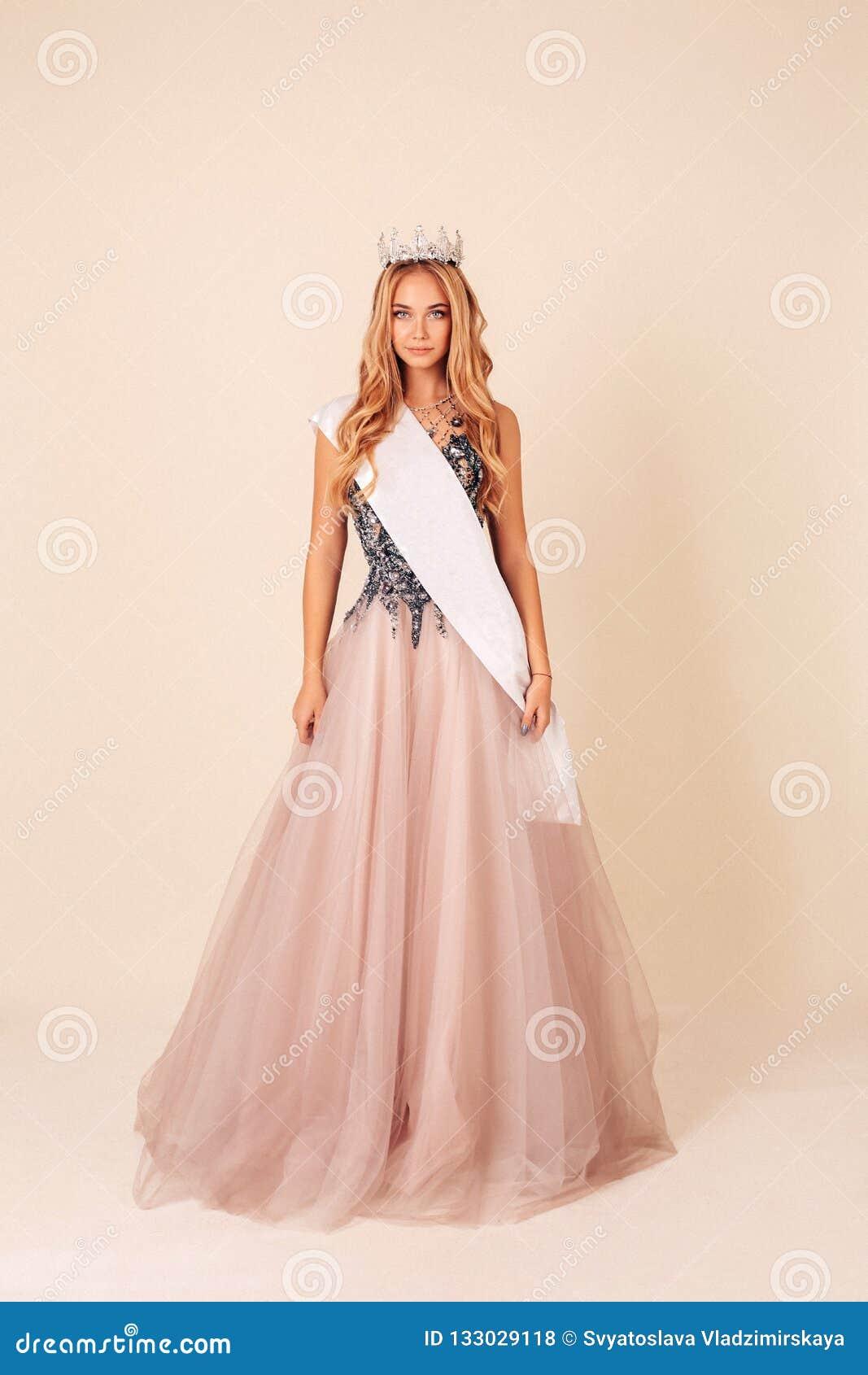 Mujer hermosa con el pelo rubio largo en vestido de noche lujoso