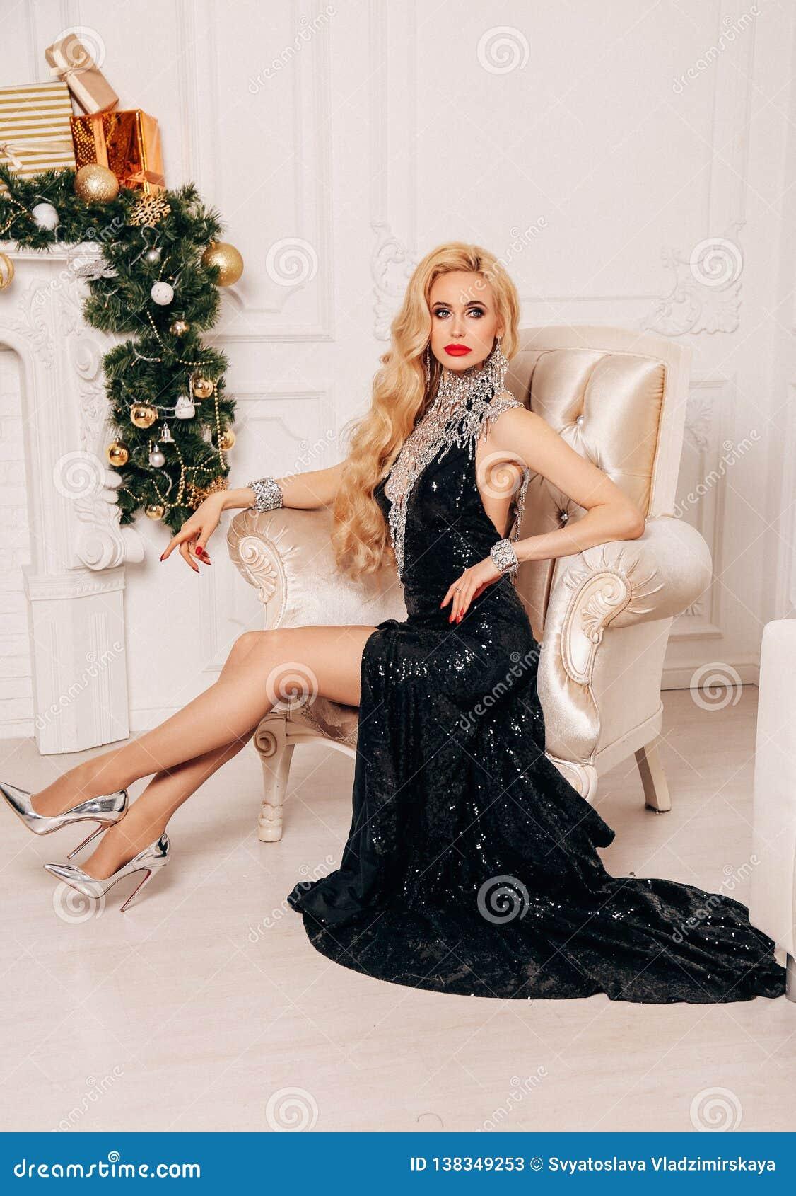 Mujer hermosa con el pelo rubio largo en el vestido elegante que presenta cerca del árbol de navidad adornado