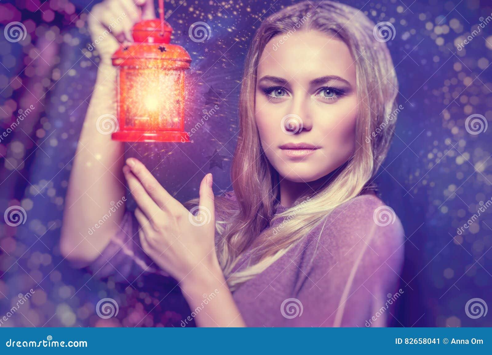 Mujer hermosa con la linterna que brilla intensamente