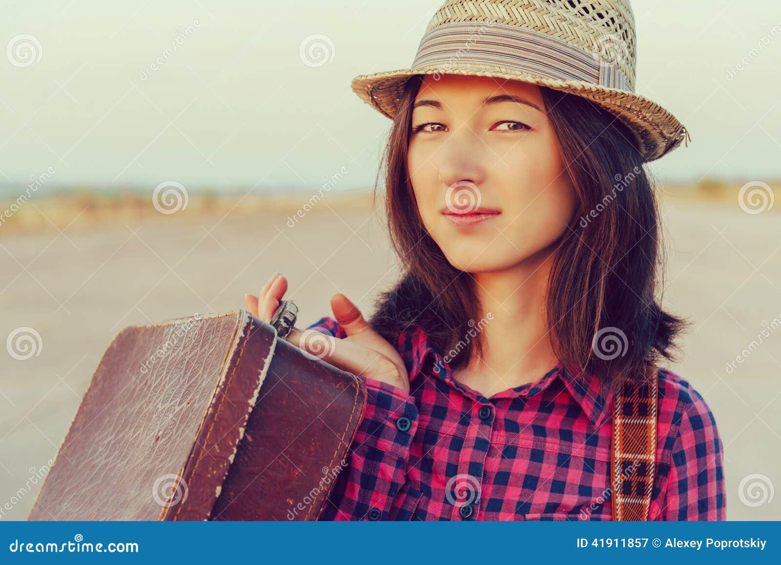 Mujer hermosa con la maleta del vintage