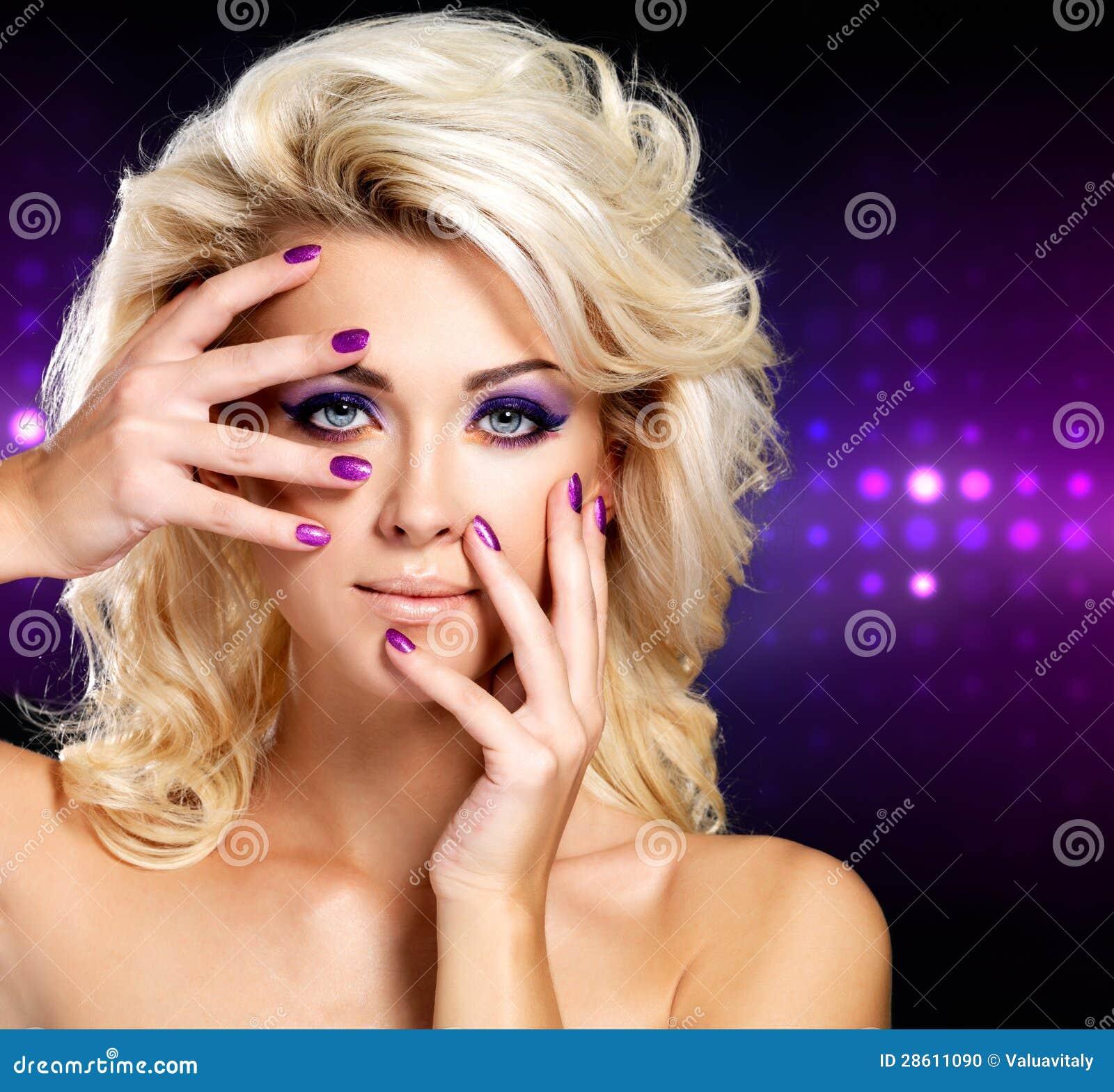 Mujer hermosa con la manicura de la belleza y el maquillaje púrpuras de ojos.