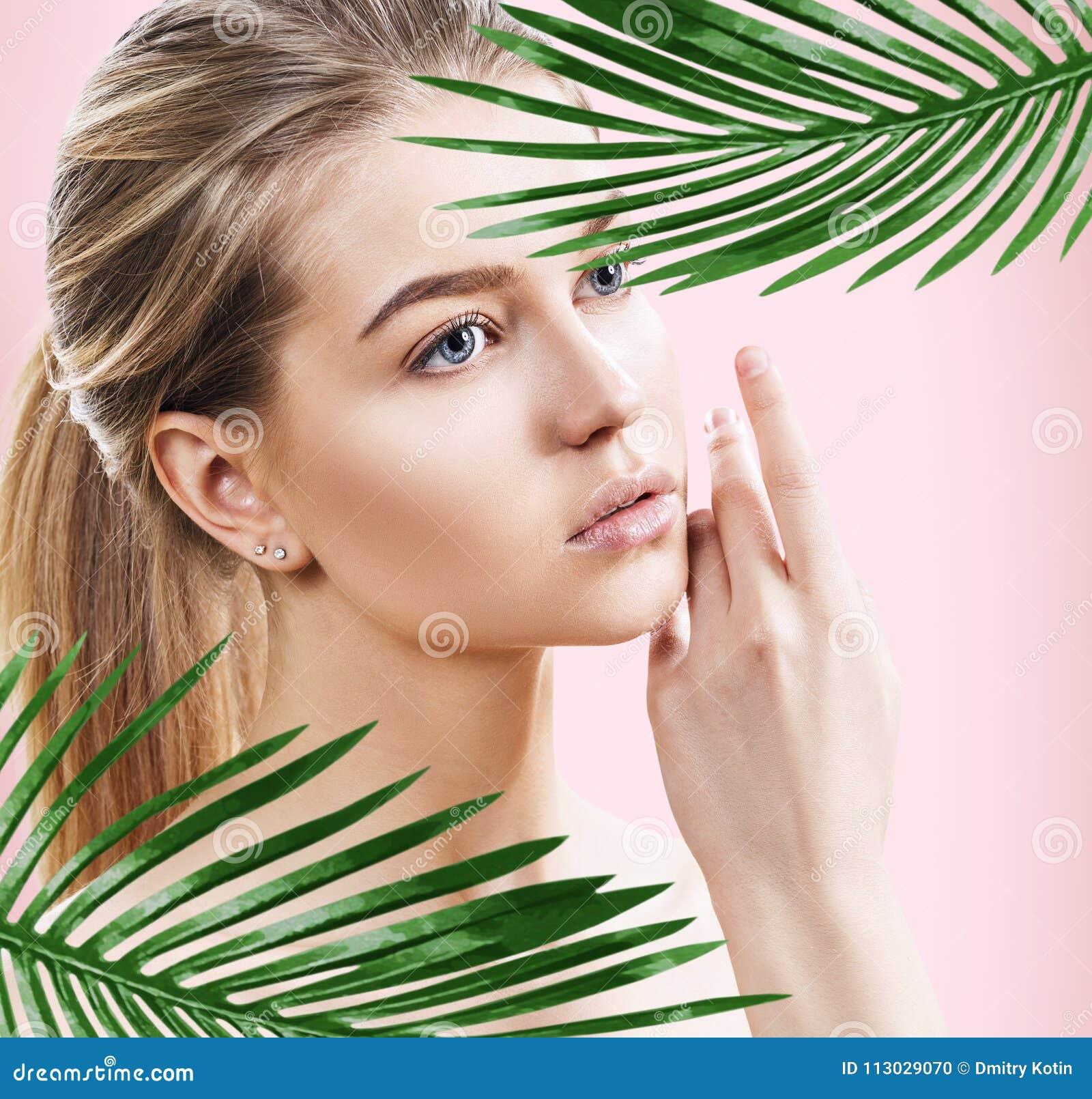 Mujer hermosa con la piel perfecta entre hojas de palma