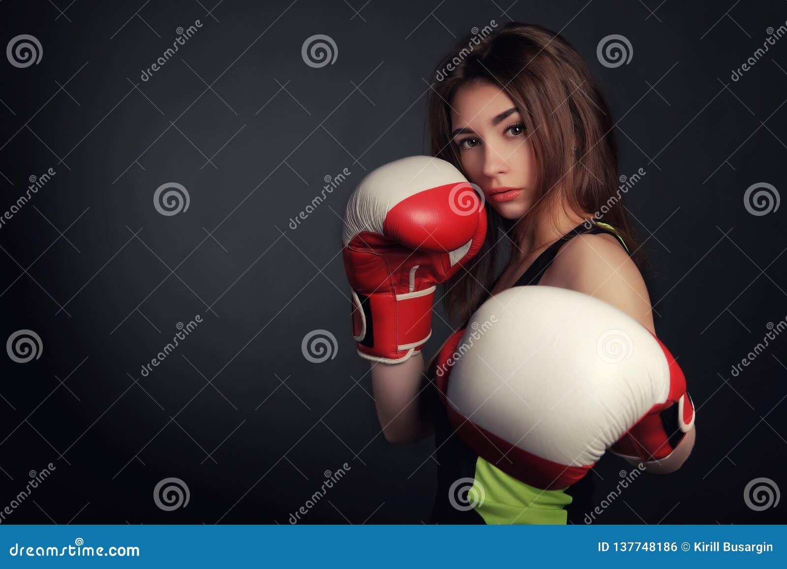 Mujer hermosa con los guantes de boxeo rojos, fondo negro
