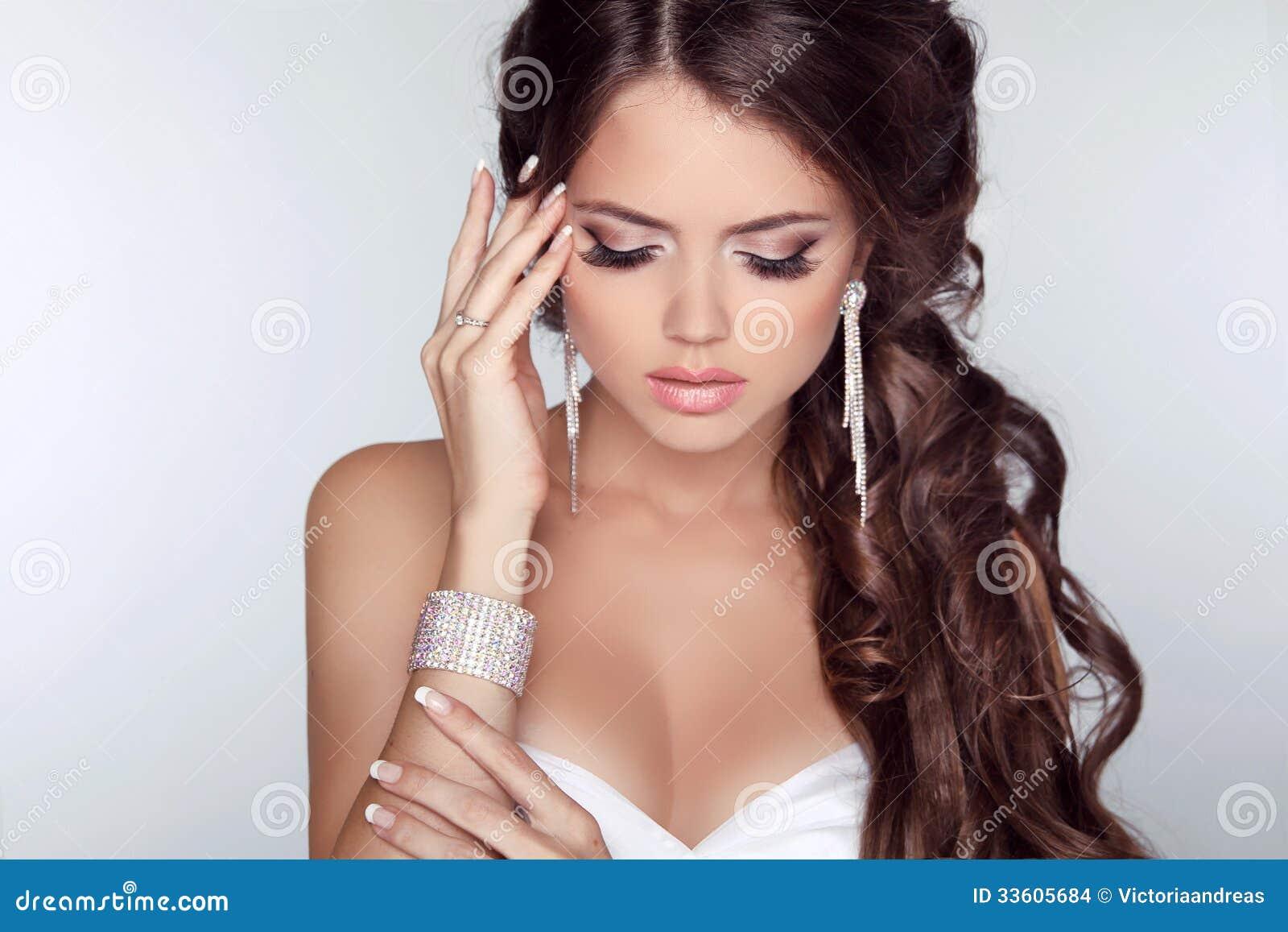 Mujer hermosa con maquillaje del pelo rizado y de la tarde aislada encendido