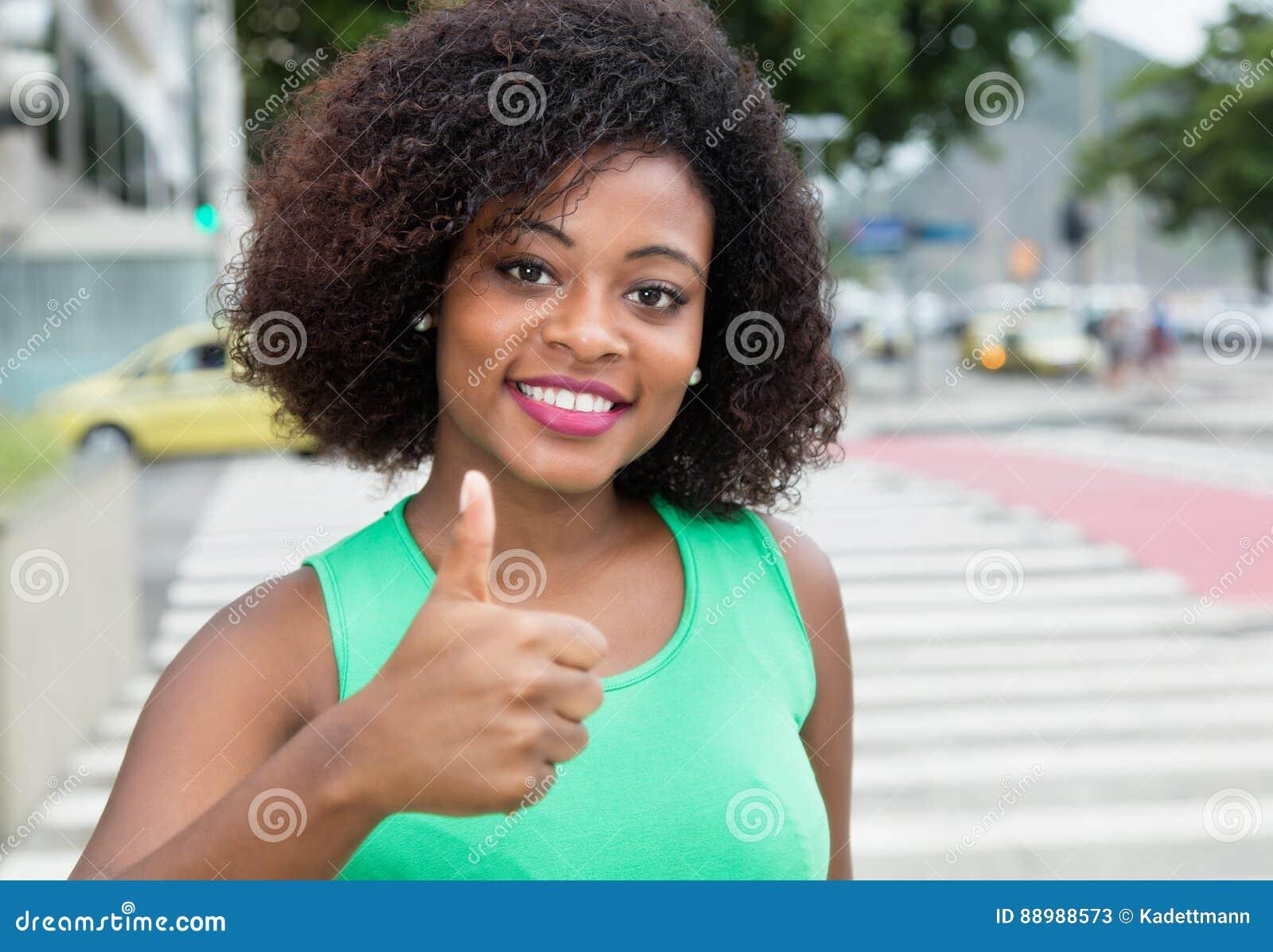 Mujer hermosa de África en una camisa verde que muestra el pulgar para arriba adentro