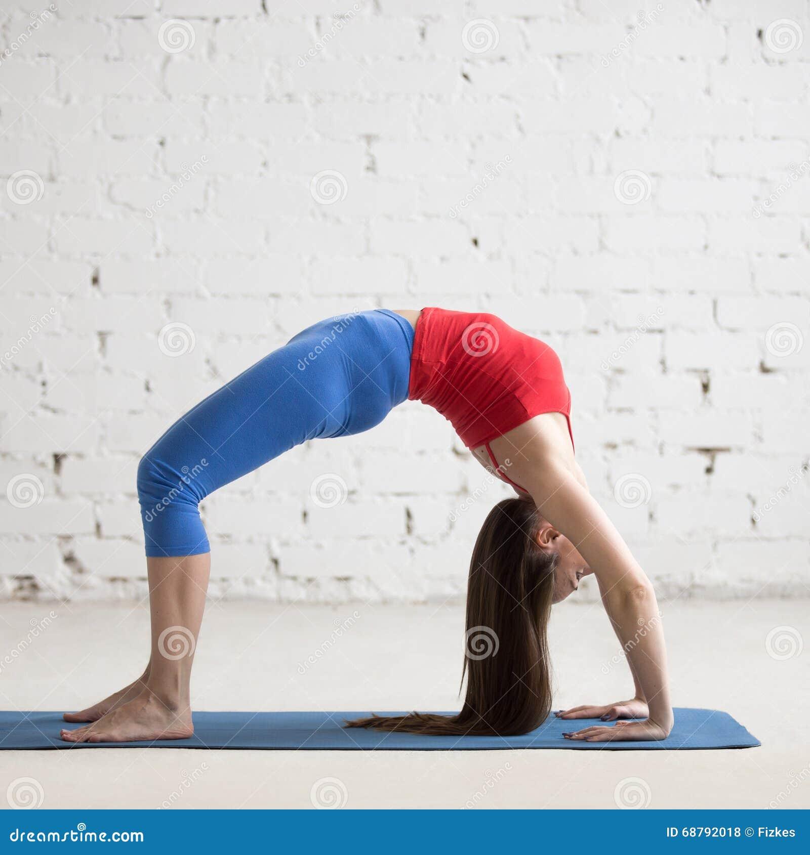 Mujer hermosa de la yoga que hace actitud del puente