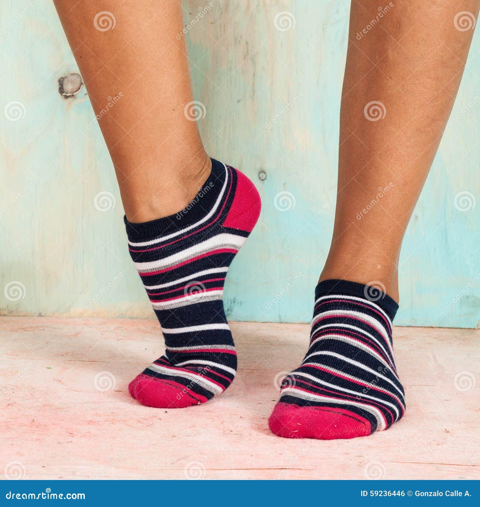 Mujer hermosa de las piernas con los calcetines que se colocan de puntillas en el piso de madera