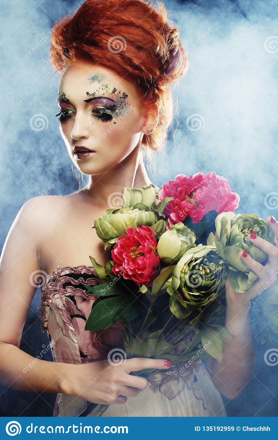 Mujer hermosa del redhair que sostiene las flores