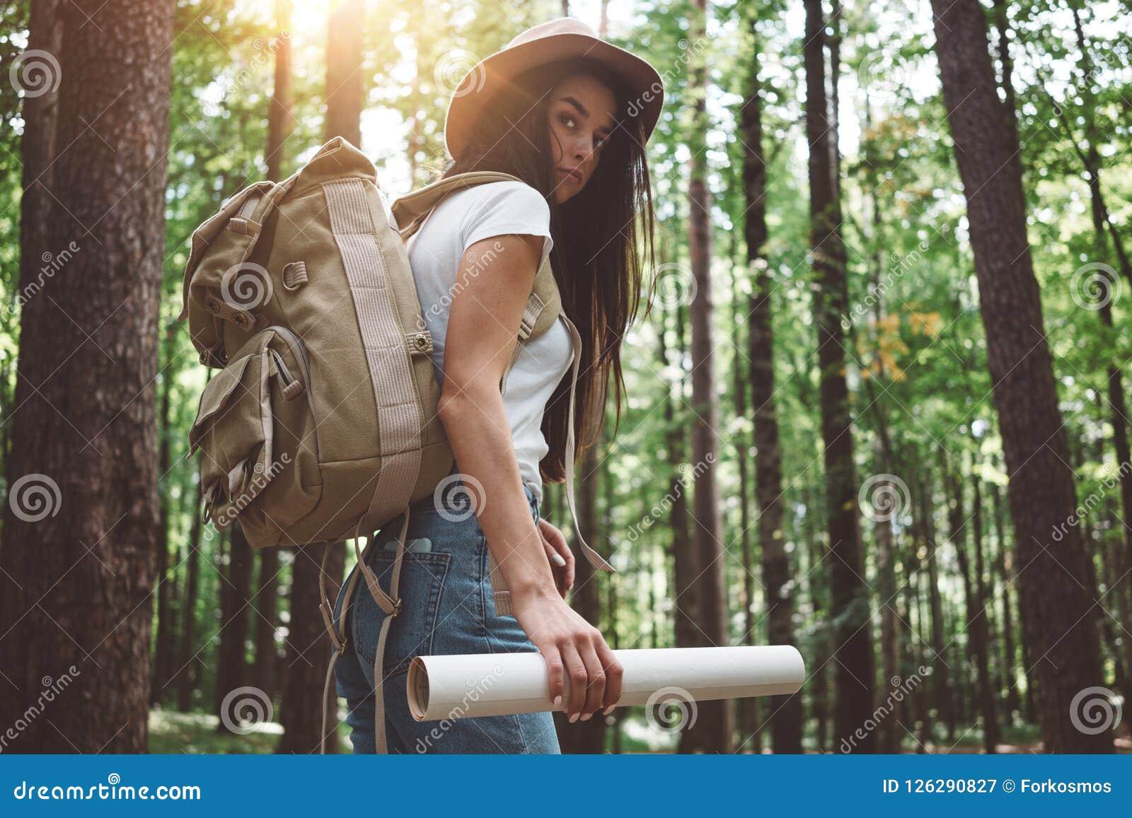 Mujer hermosa del viajero con la mochila y el sombrero que se colocan en la muchacha joven del inconformista del bosque que camin