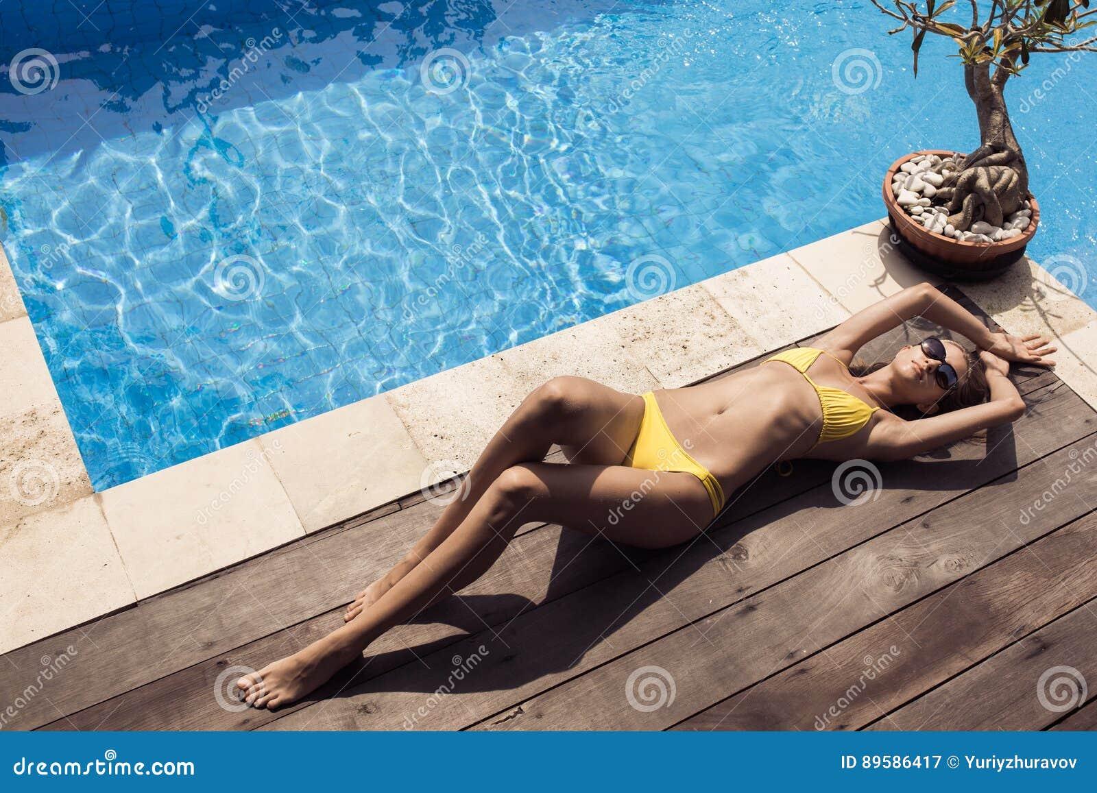 061144df57d6 Mujer hermosa delgada joven en bikini amarillo que toma el sol cerca de  piscina