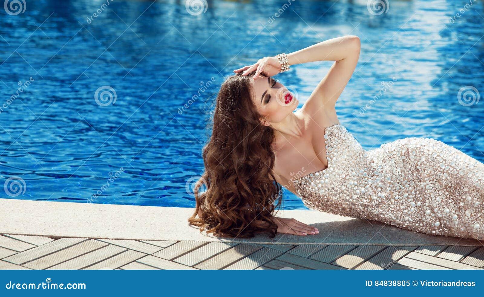 Mujer hermosa en alineada elegante Mentira morena atractiva por el interruptor azul