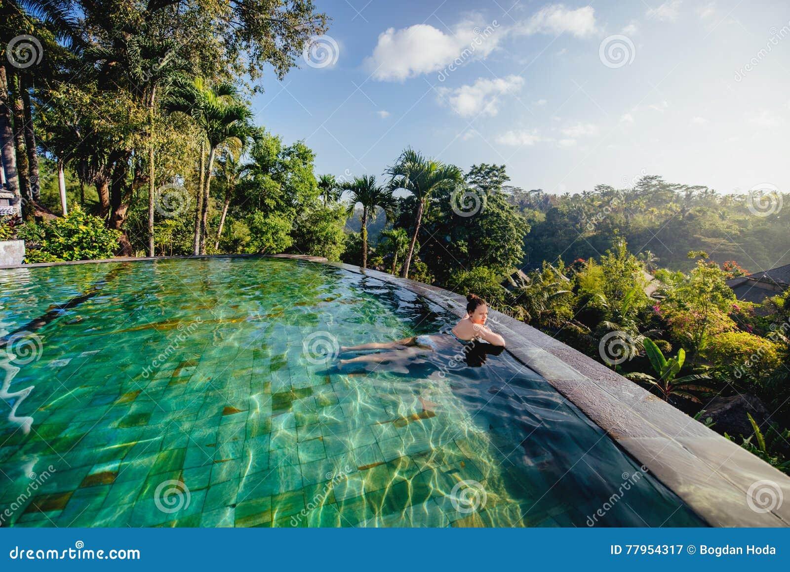Mujer hermosa en centro turístico lujoso Chica joven que toma un baño y que se relaja en la piscina del infinito