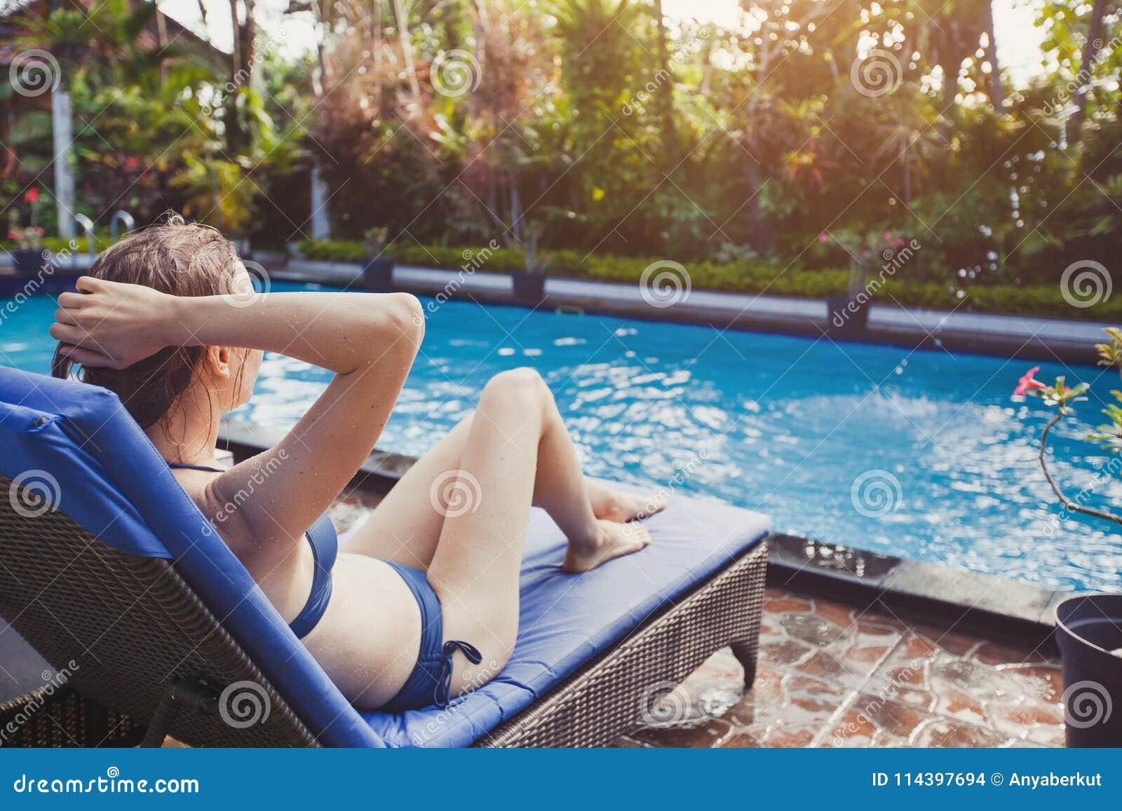 Mujer hermosa en el bikini que se relaja en silla de cubierta cerca de piscina en hotel