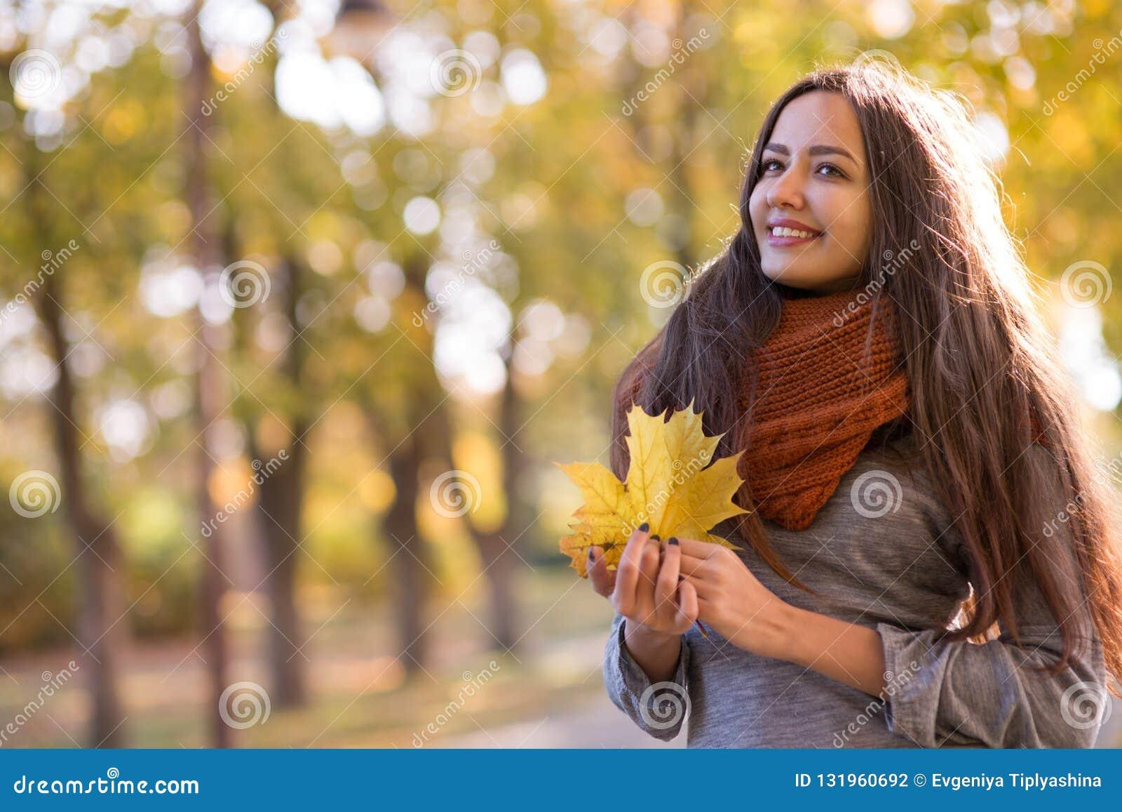 Mujer hermosa en el parque del otoño