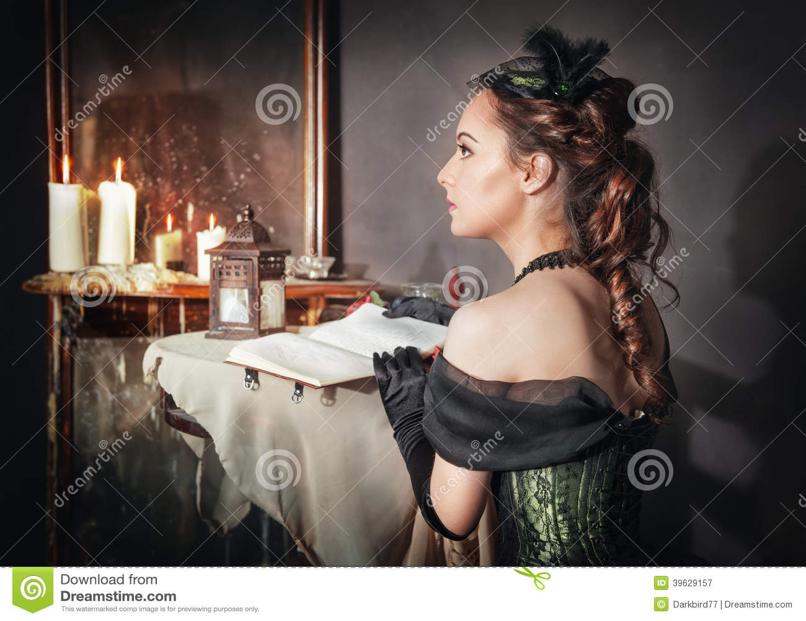 Mujer hermosa en espejo cercano del vestido medieval