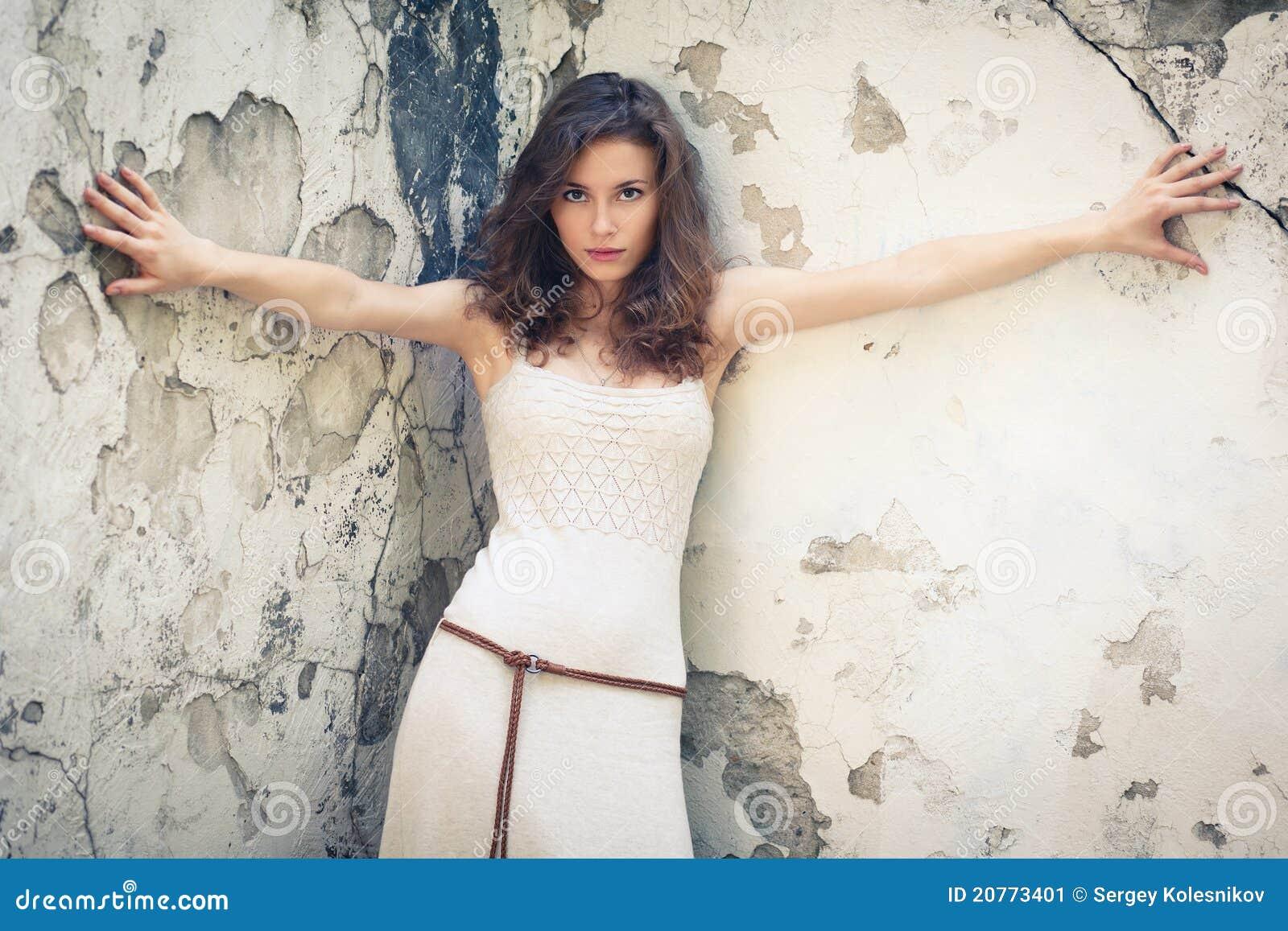Mujer hermosa en fondo de la pared vieja