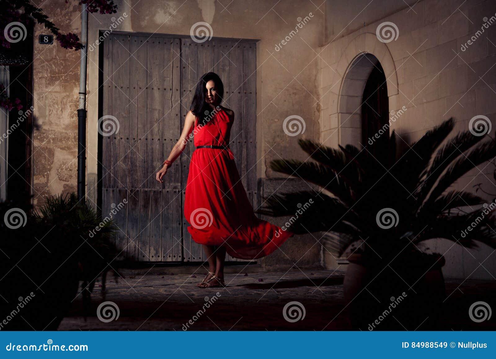Mujer hermosa en la presentación roja del vestido