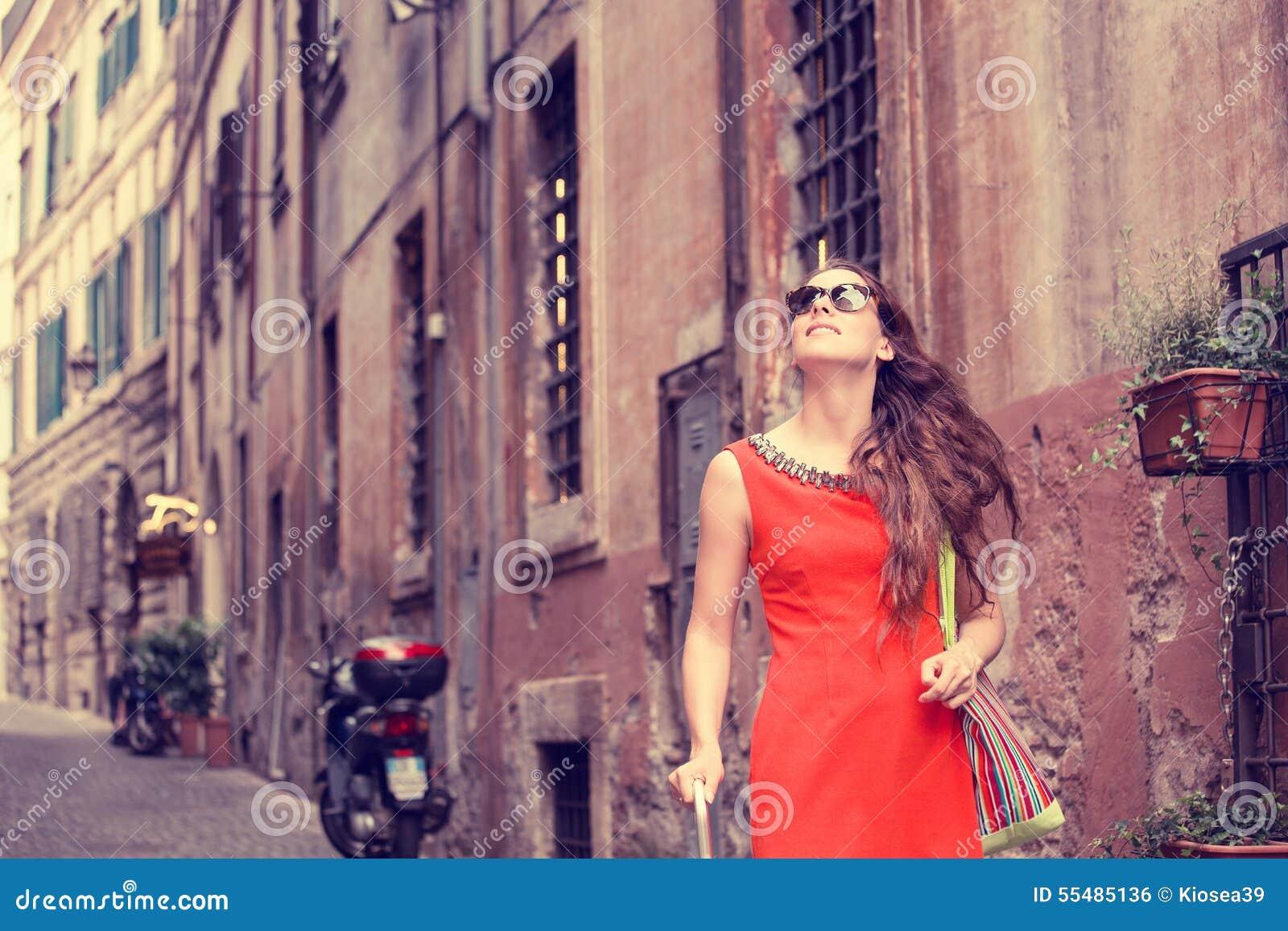 Mujer hermosa en la sonrisa que camina del vestido rojo del verano en Roma, Italia