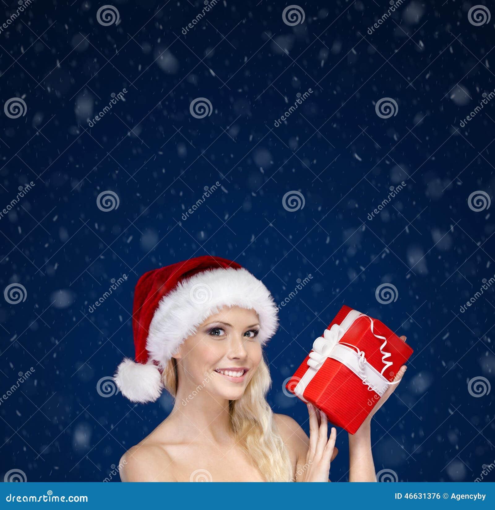 Mujer hermosa en las manos del casquillo de la Navidad presentes