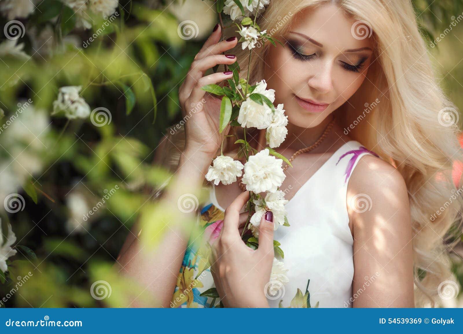 Mujer hermosa en parque cerca de las rosas florecientes de Bush