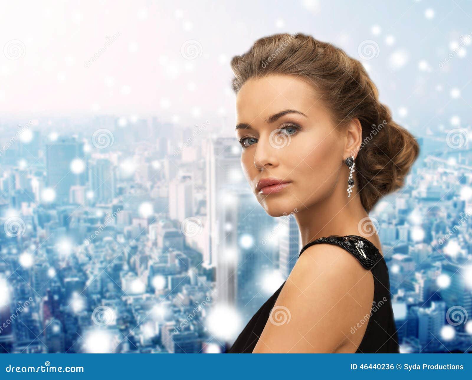 Mujer hermosa en pendientes que llevan del vestido de noche