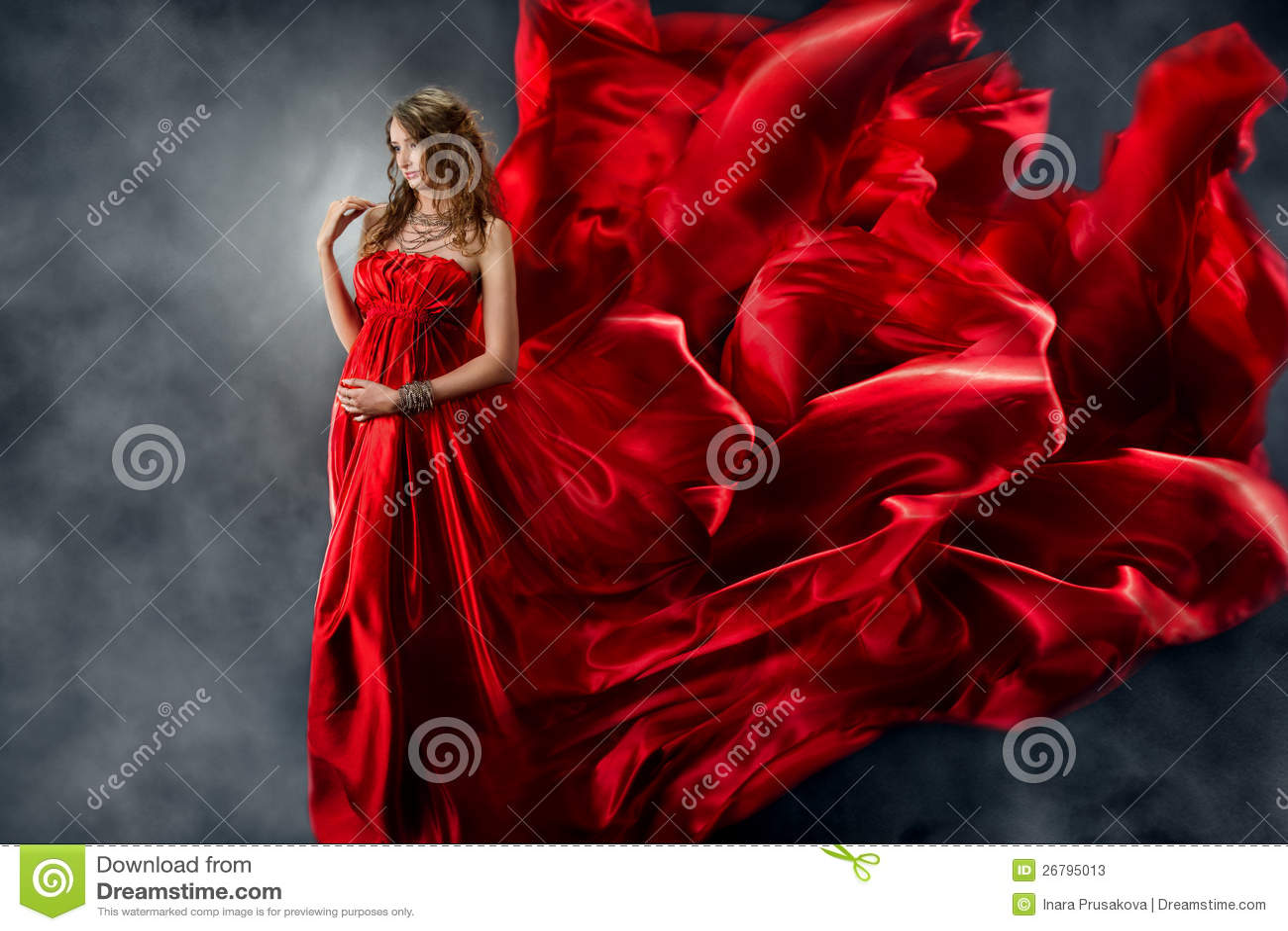 Mujer hermosa en seda que agita roja como llama