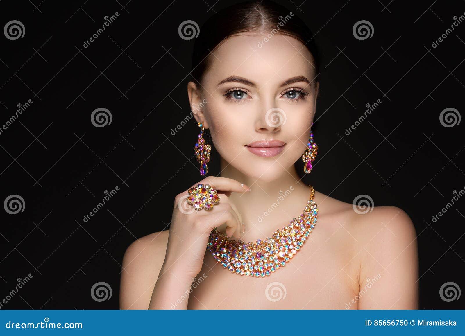 Mujer hermosa en un collar, pendientes y anillo Modelo en joya