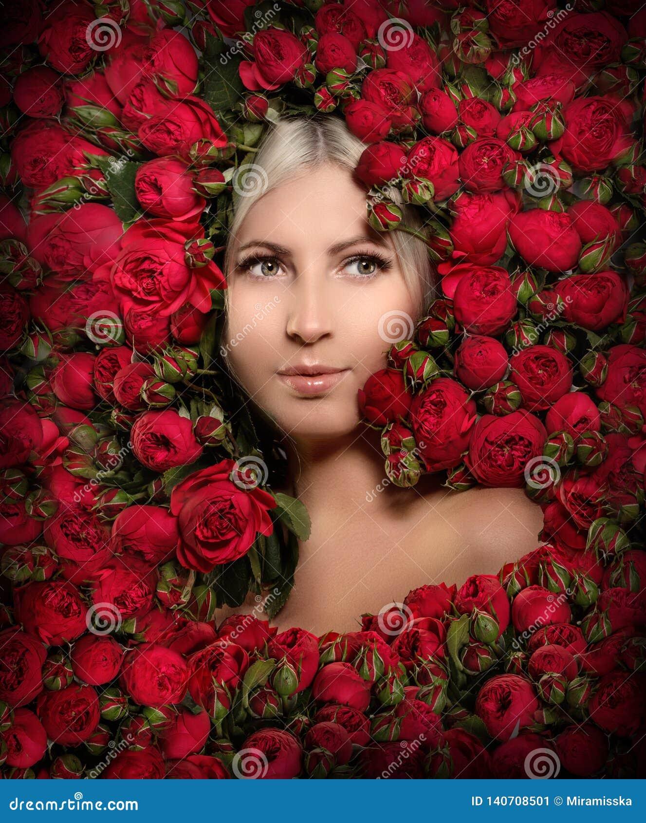 Mujer hermosa en un marco de flores Chica joven con las rosas rojas de la peonía