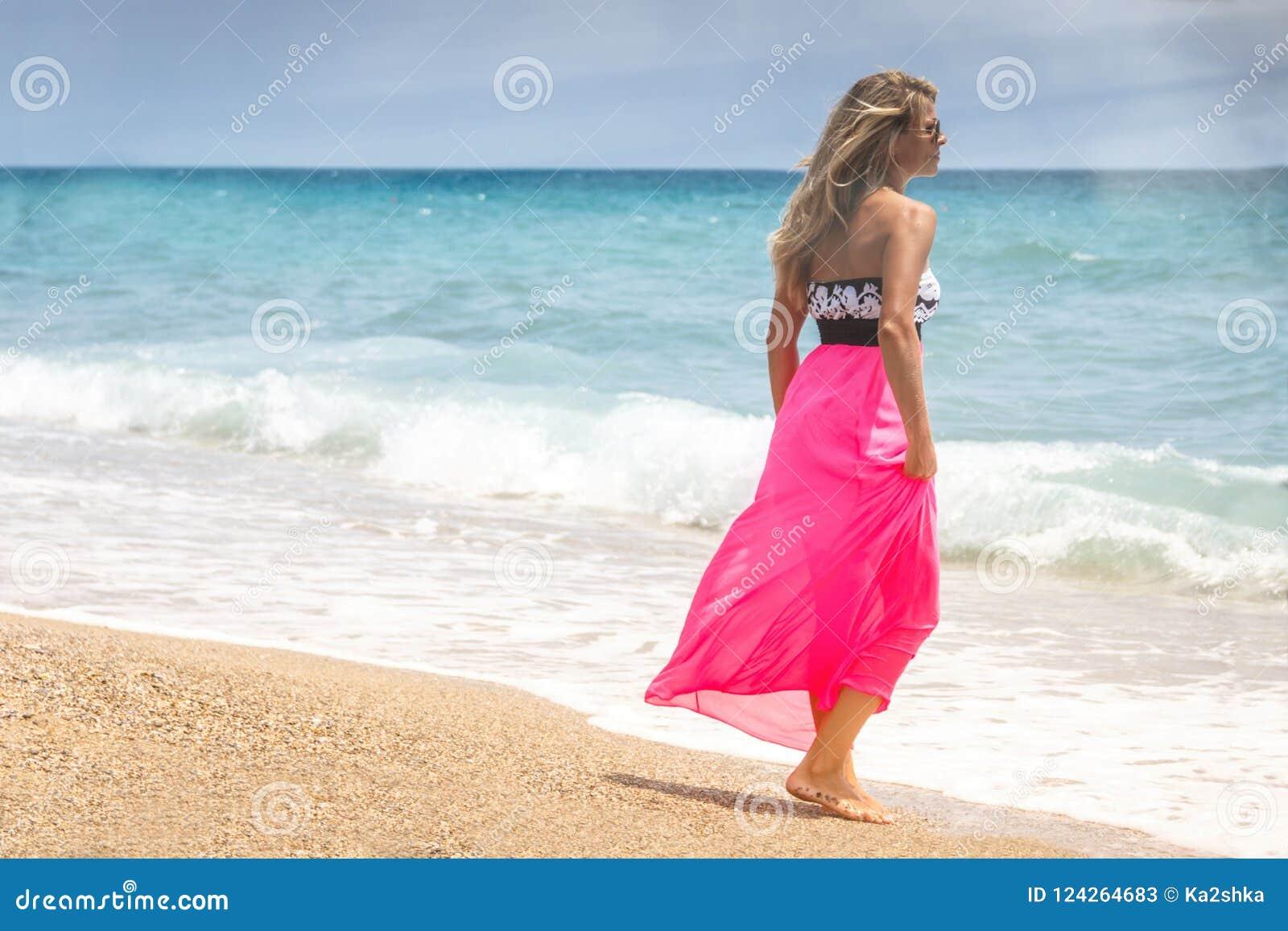 Mujer hermosa en un vestido que camina en la playa Mujer relajada que respira el aire fresco, mujer sensual emocional cerca del m