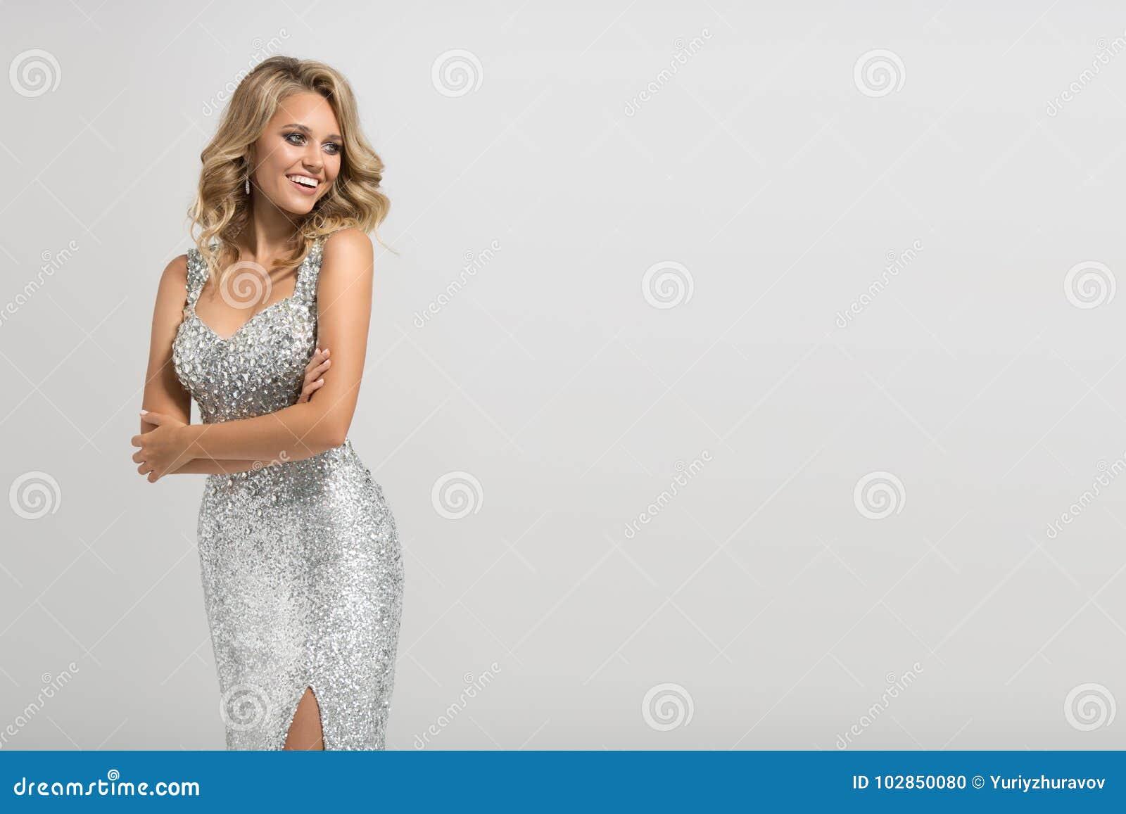 Mujer hermosa en vestido de plata brillante