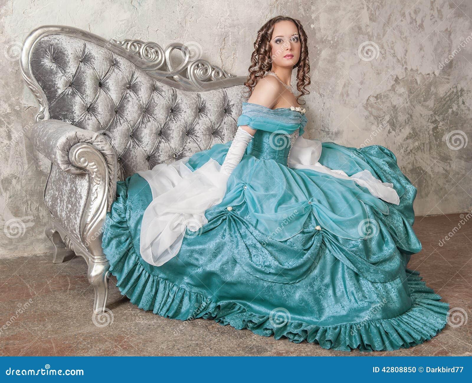 Mujer hermosa en vestido medieval en el sofá
