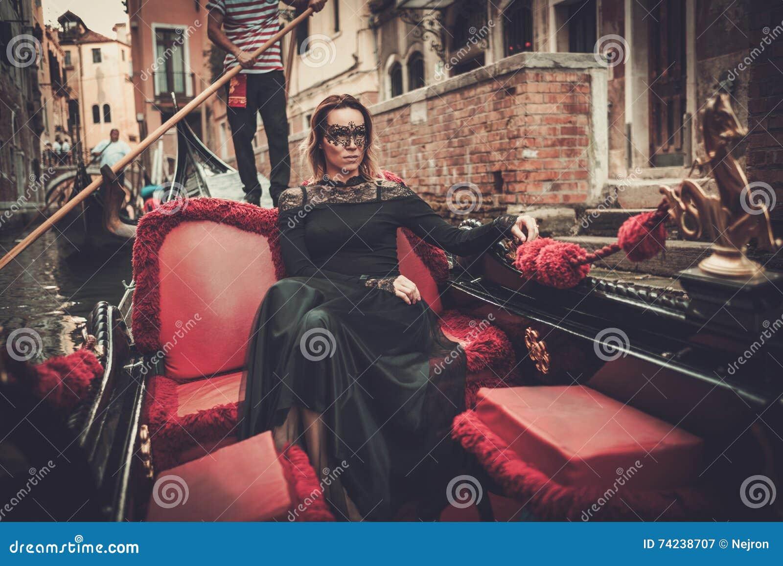 Mujer hermosa en vestido negro con el montar a caballo carnaval de la máscara en la góndola